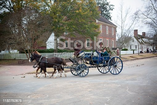 'Williamsburg, Va, USA - December 5, 2018. . The stage wagon takes visitors past the historic Governor's Palace.