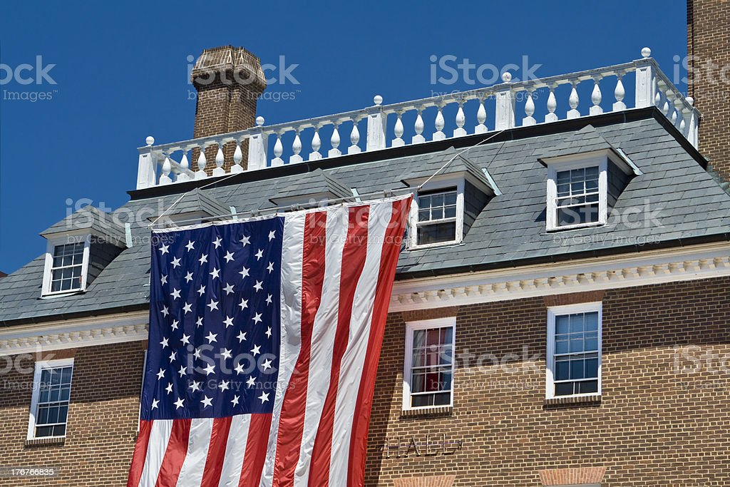 Colonial Revival Style Building with Large American Flag Blue Sky stock photo