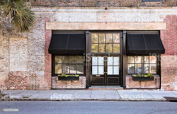Colonial Storefront with black awnings with old brick wall, window boxes and cracked pavement.