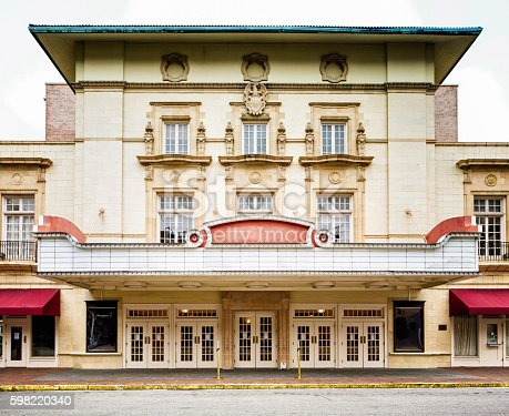 Colonial style southern USA movie theater concert hall facade with curb and sidewalk.