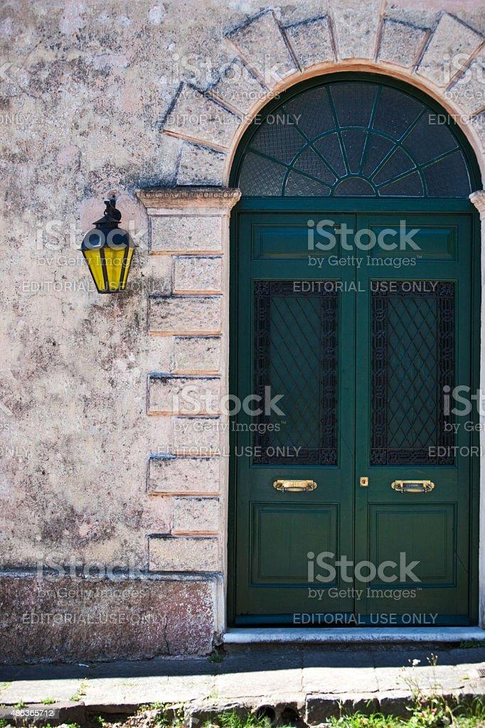 Colonial luminária amarela rua Hanged na parede e porta Verde - foto de acervo