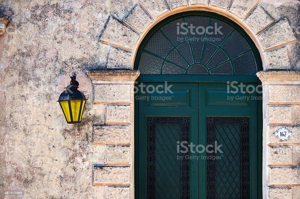 Colonial luminária amarela rua Hanged na parede e porta Verde foto royalty-free