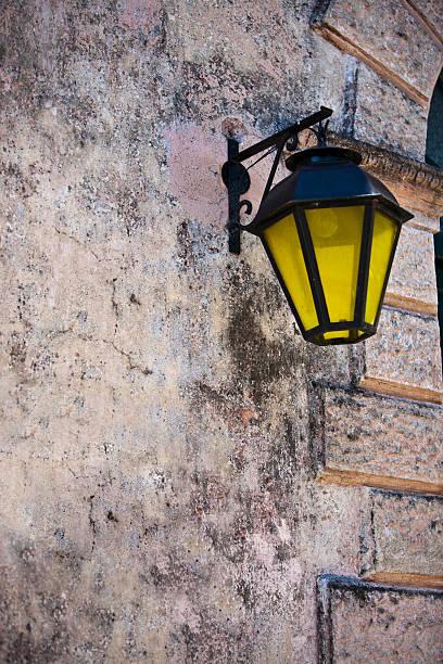 Colonial luminária amarela rua Hanged na parede - foto de acervo