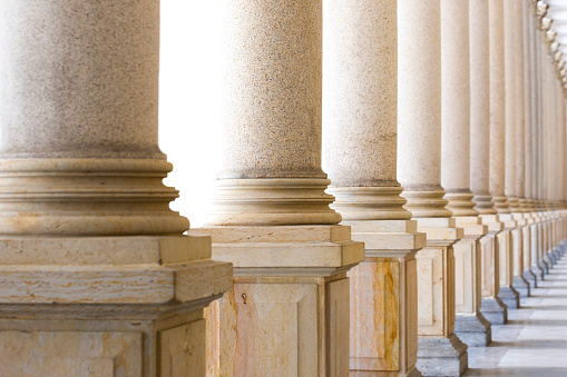 istock Colonnade, row of classical stone columns, background with copy spaced 1013918710