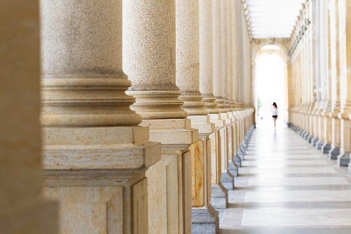 istock Colonnade, row of classical stone columns, background with copy spaced 1032922614