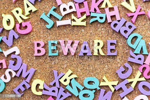 istock Color alphabet in word beware with another letter as frame on cork board background 1125898183