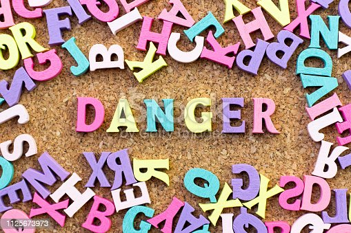 istock Color alphabet in word danger with another letter as frame on cork board background 1125673973
