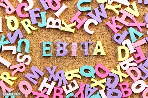 istock Color alphabet in word EBITA (abbreviation of  earnings before interest, taxes and amortization) with another letter as frame on cork board background 1140141324