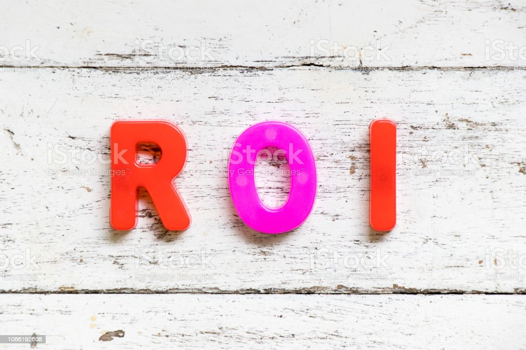 Color alphabet in word ROI (Abbbreviation of Return on Investment) on grunge old white wood background stock photo
