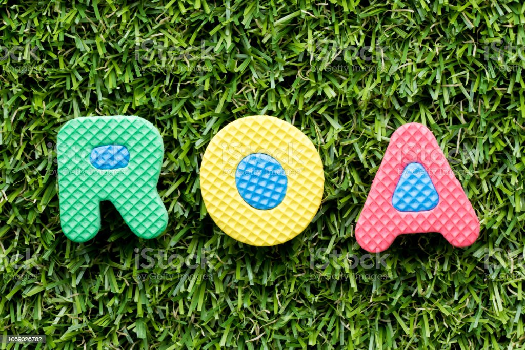 Color alphabet letter in word ROA (Abbbreviation of Return on assets) on artificial green grass background stock photo