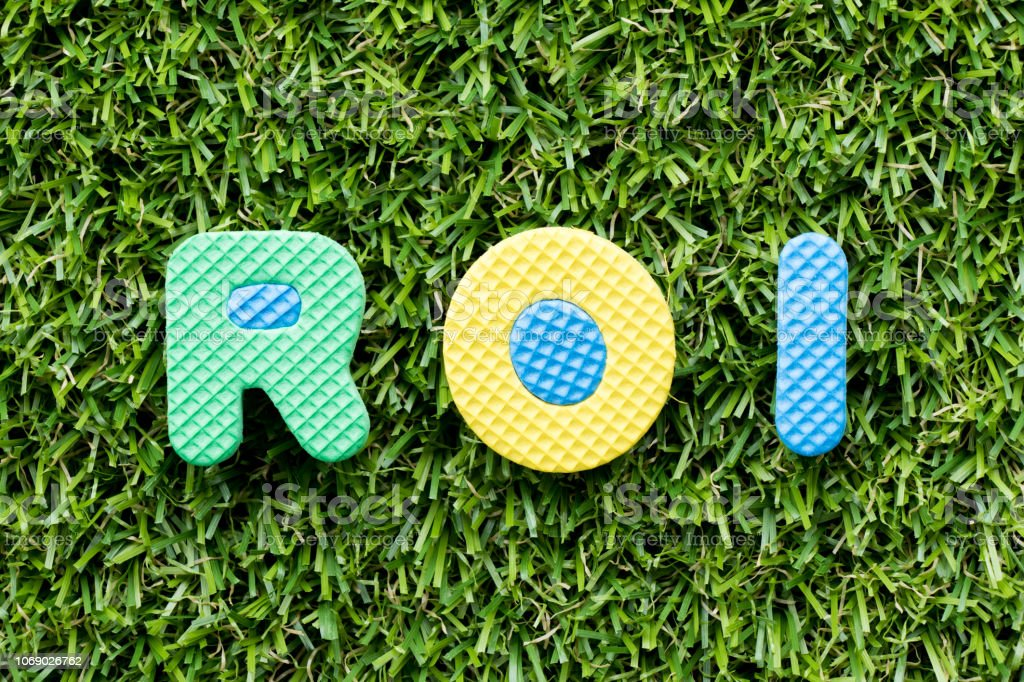 Color alphabet letter in word ROI (Abbreviation of Return on Investment) on artificial green grass background stock photo