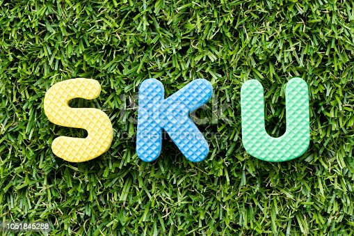 istock Color alphabet letter in word SKU (abbreviation of stock keeping unit) on artificial green grass background 1051845288