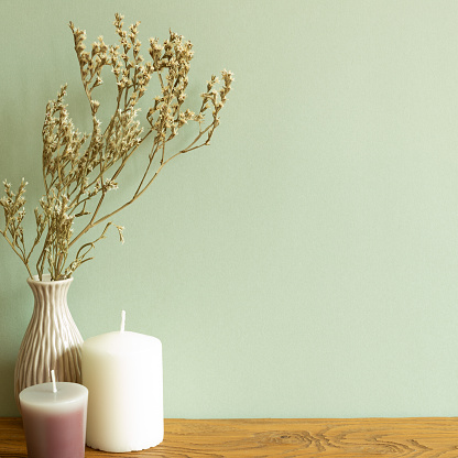 Color candles and vase of dry flowers on wooden table. green wall background. home interior