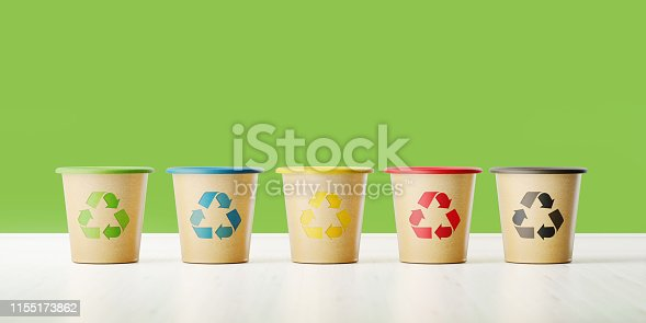 Color coded garbage bins with recycling symbols in front of a green wall. Horizontal composition with copy space.