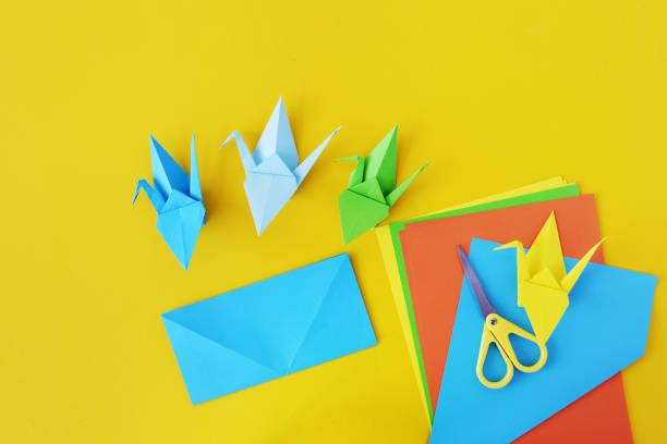 farbe-krane des origami aus papier auf einem gelben hintergrund. - origami anleitungen stock-fotos und bilder