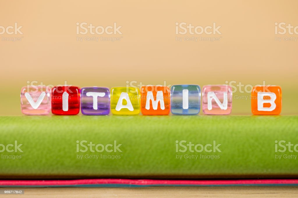 color cube figure with word vitamin b on green book stock photo