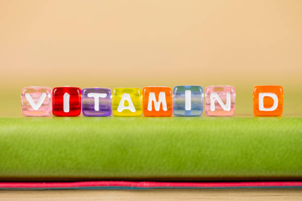 color cube figure with word vitamin d on green book stock photo