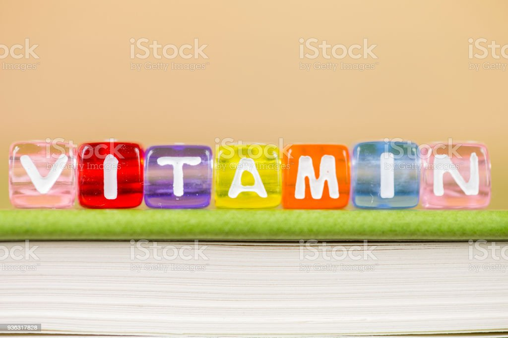 color cube figure with word vitamin on green book stock photo