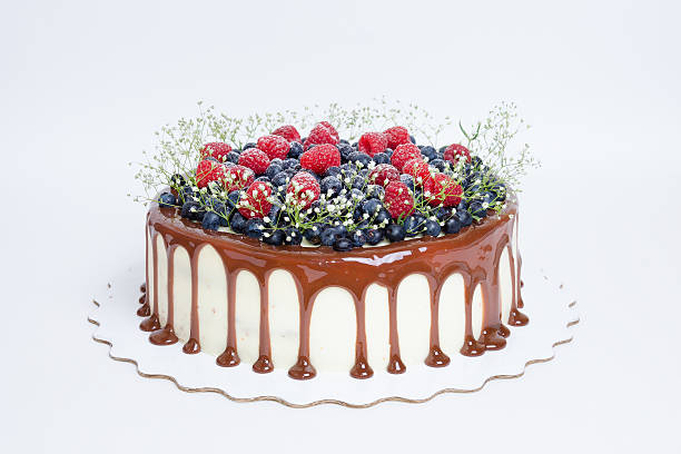 color drip cake with blueberries and raspberries stock photo