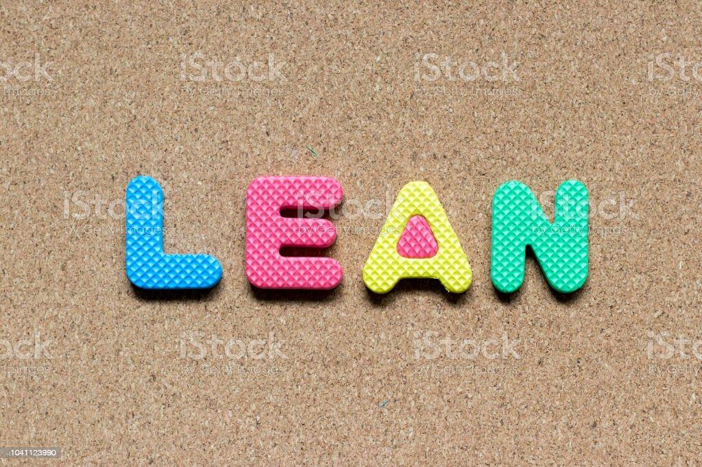Color foam alphabet in word lean on cork board background stock photo