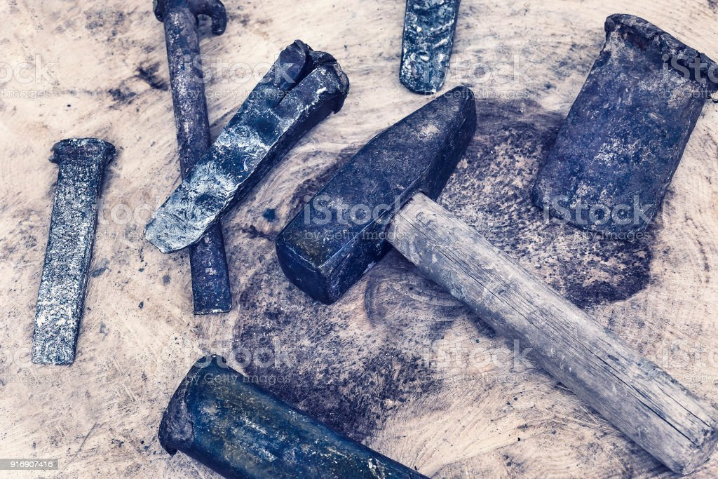 Color graded image of a hammer and old metal wedges stock photo