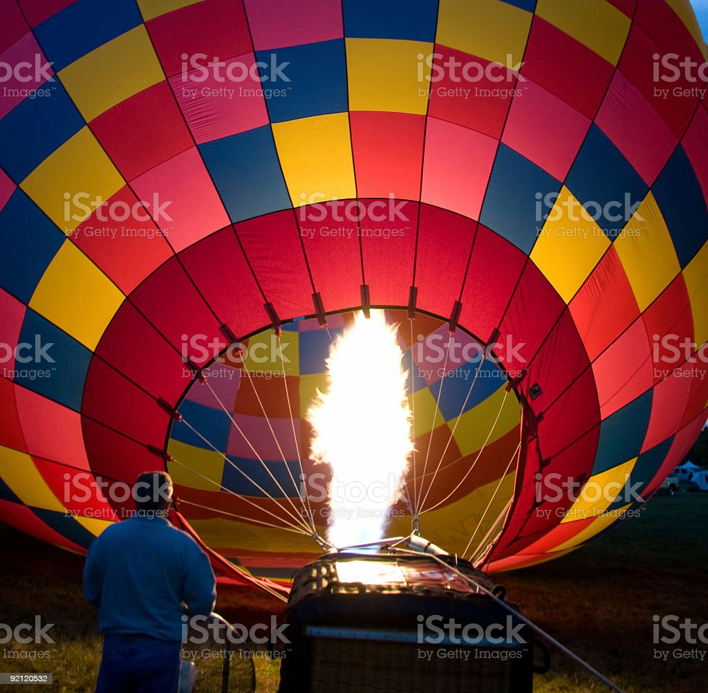 Color hot air balloon getting heated to take off stock photo