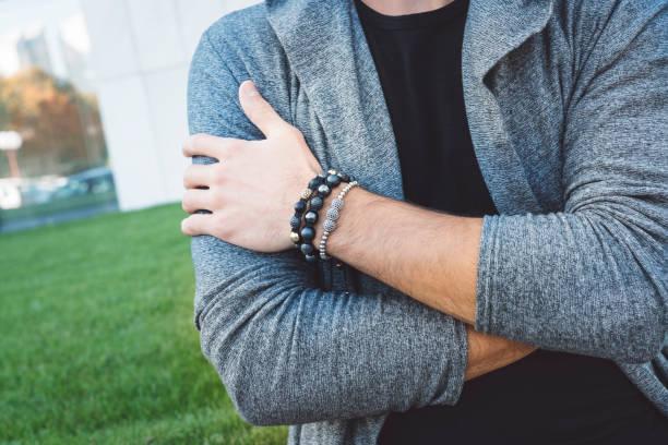 farbbild des erwachsenen männlichen hand mit armband - a zone armband stock-fotos und bilder