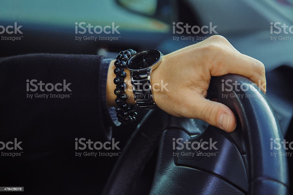 Color image of adult male hand with watch and bracelet stock photo
