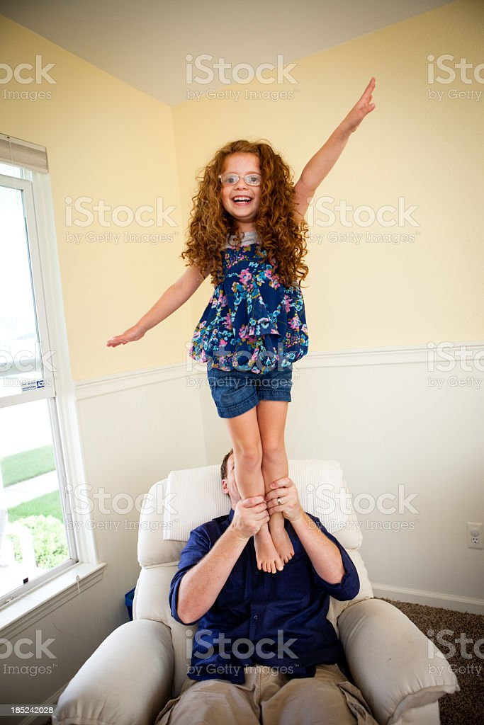 Color Image of Dad Holding Little Daughter in the Air royalty-free stock photo