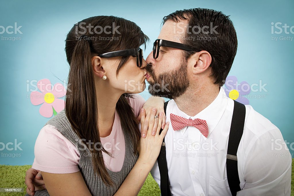 Color Image of Happy, Nerdy Couple Shyly Kissing stock photo