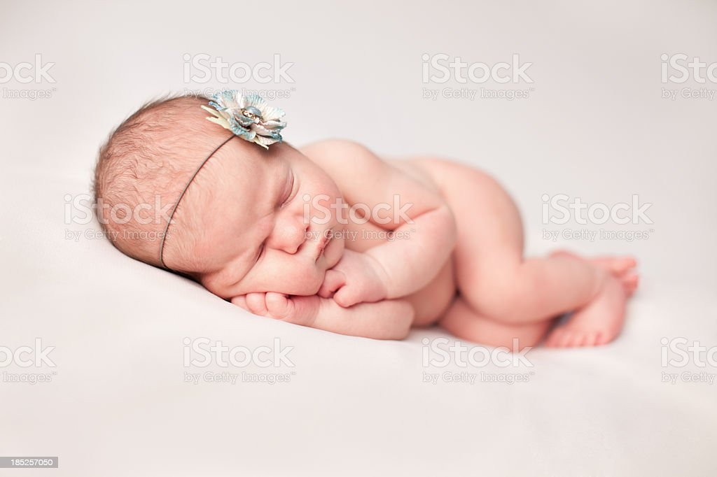 Color Image of Peaceful Newborn Baby Girl Wearing Flower Headband royalty-free stock photo