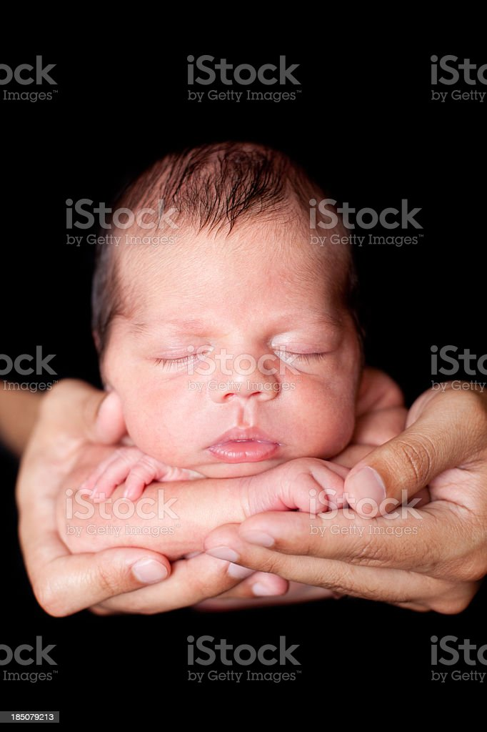 Color Image of Peaceful Newborn Sleeping in Father's Hands stock photo