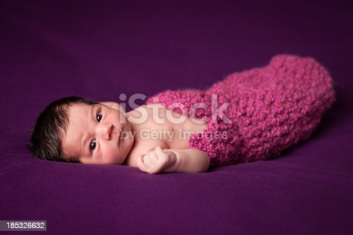 Color image of a precious, awake newborn baby girl, wrapped in a blanket, with purple background.