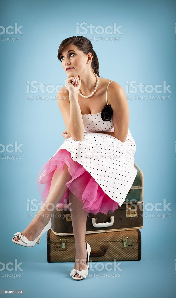 Color Image of Retro Gal Sitting on Vintage Suitcases royalty-free stock photo