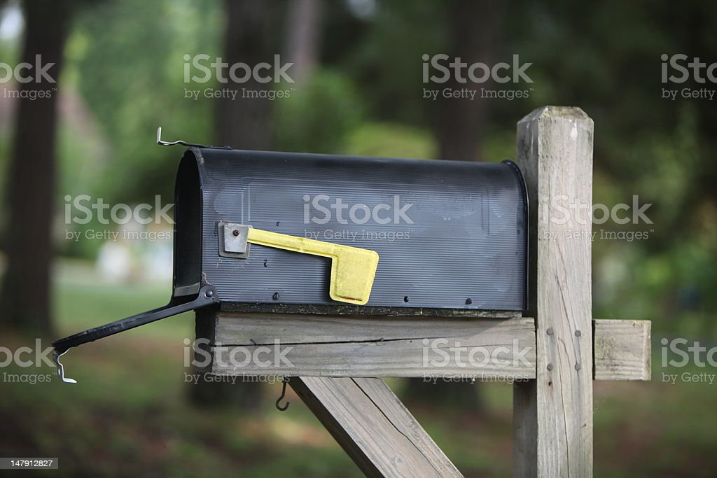 Color image of rural black mailbox,  yellow flag, open door stock photo