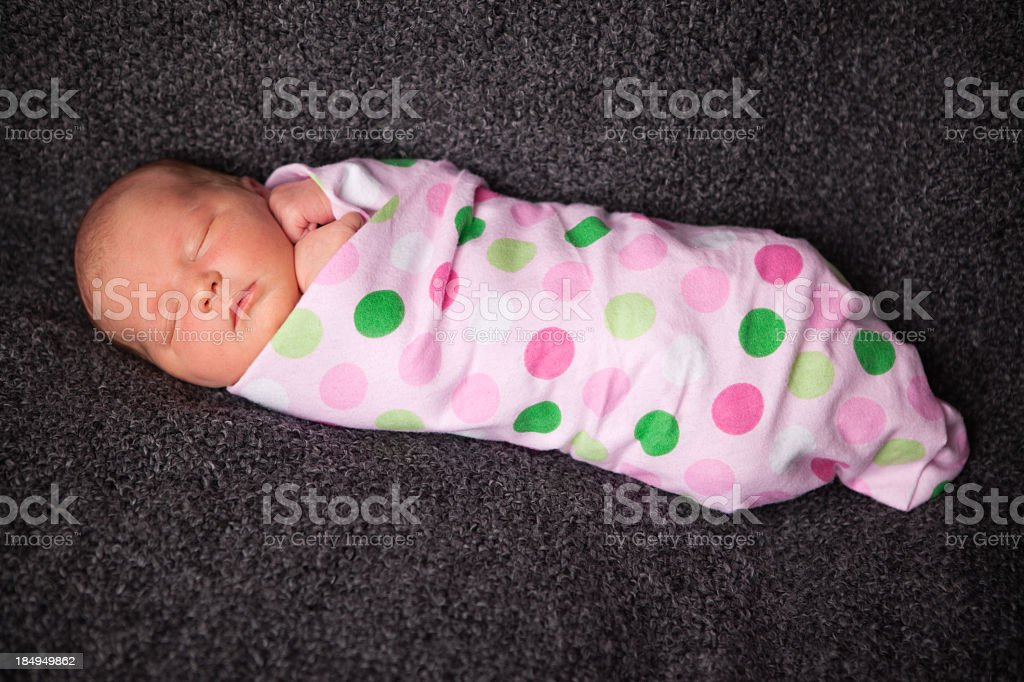 Color Image of Sleeping Newborn Baby Girl Wrapped in Blanket Color image of a sleeping newborn baby girl wrapped in polka dot blanket, with textured, black background. 0-1 Months Stock Photo