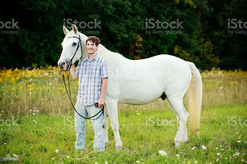 Color Image of Teenage Boy Standing By His White Horse stock photo