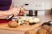 istock Color Image of Woman Peeling Potatoes in Her Kitchen 175412489