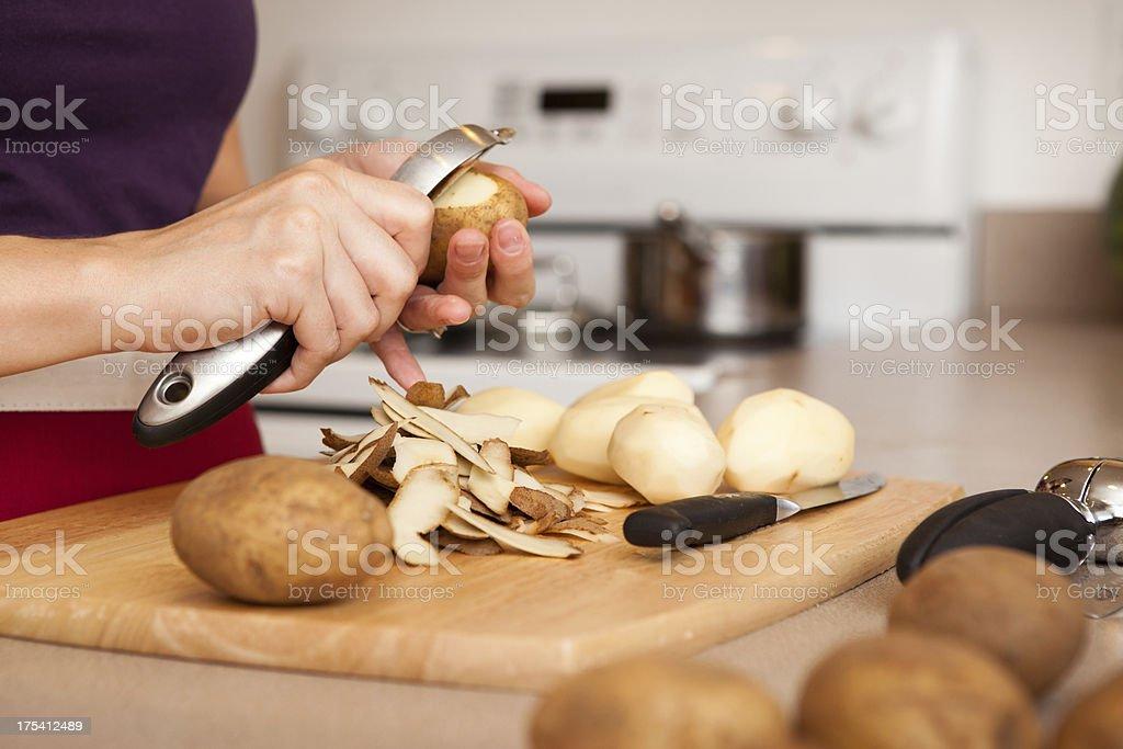 Imagem colorida de mulher de Peeling batatas em sua cozinha - foto de acervo