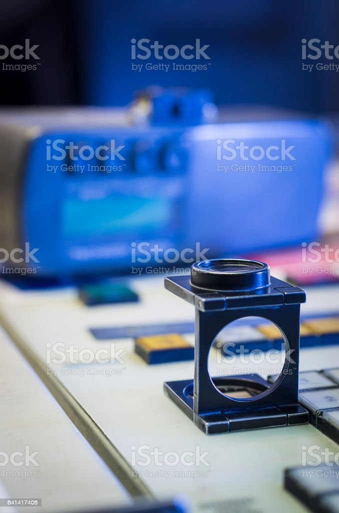 Color management process with magnifying glass and densitometer stock photo