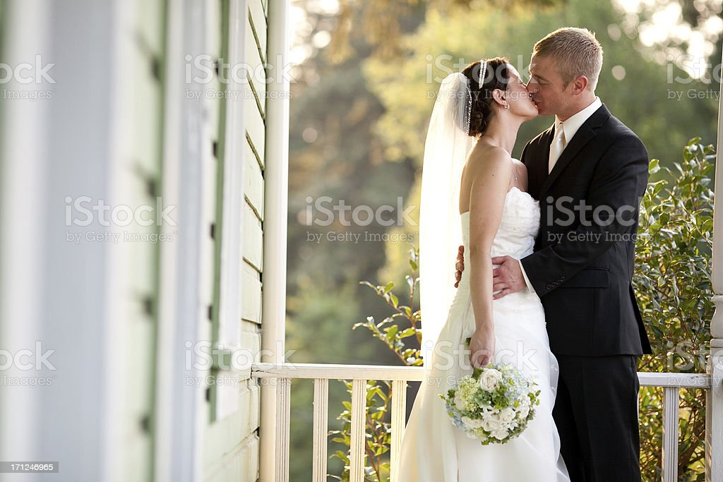 Color Newlyweds Kissing  On Country House Porch Wooded Background stock photo