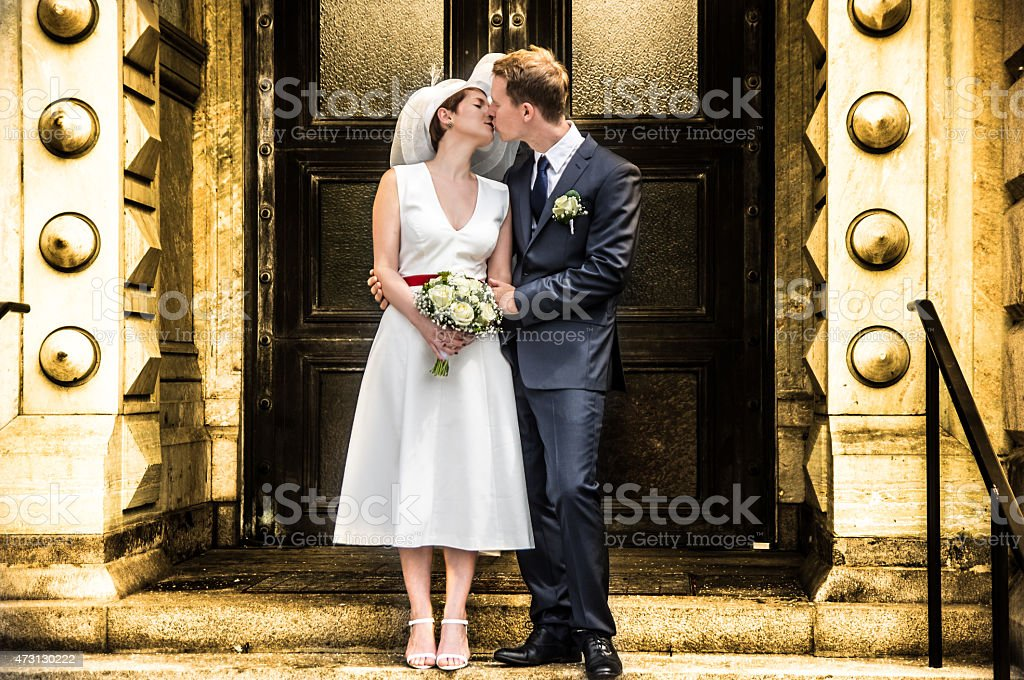 Color Newlyweds Kissing outside a church stock photo
