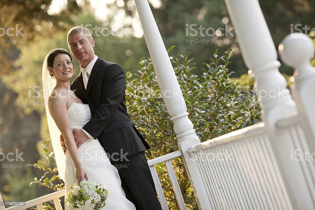 Color Newlyweds Posing Together On Country House Porch Wooded Background stock photo