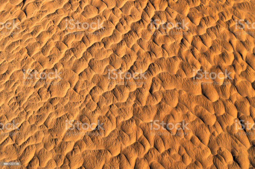 Color of sunset on the desert surface. Natural texture and background of the desert. Sand patterns royalty-free stock photo