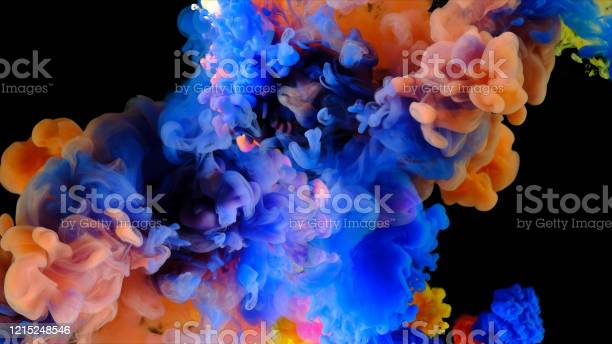 Photo of Color paint drops mixing in water, abstract color mixing in water slow motion, drop of Ink color falling on water