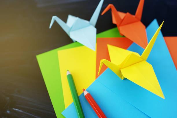 kraniche aus papier origami aus papier auf einem schwarzen hintergrund farbe - origami anleitungen stock-fotos und bilder
