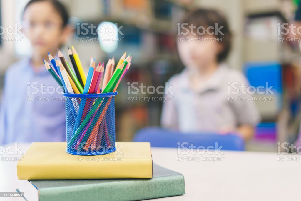 Color Pencils In A Pencil Case At Table With Kids In Library Blurred  Background. Concept