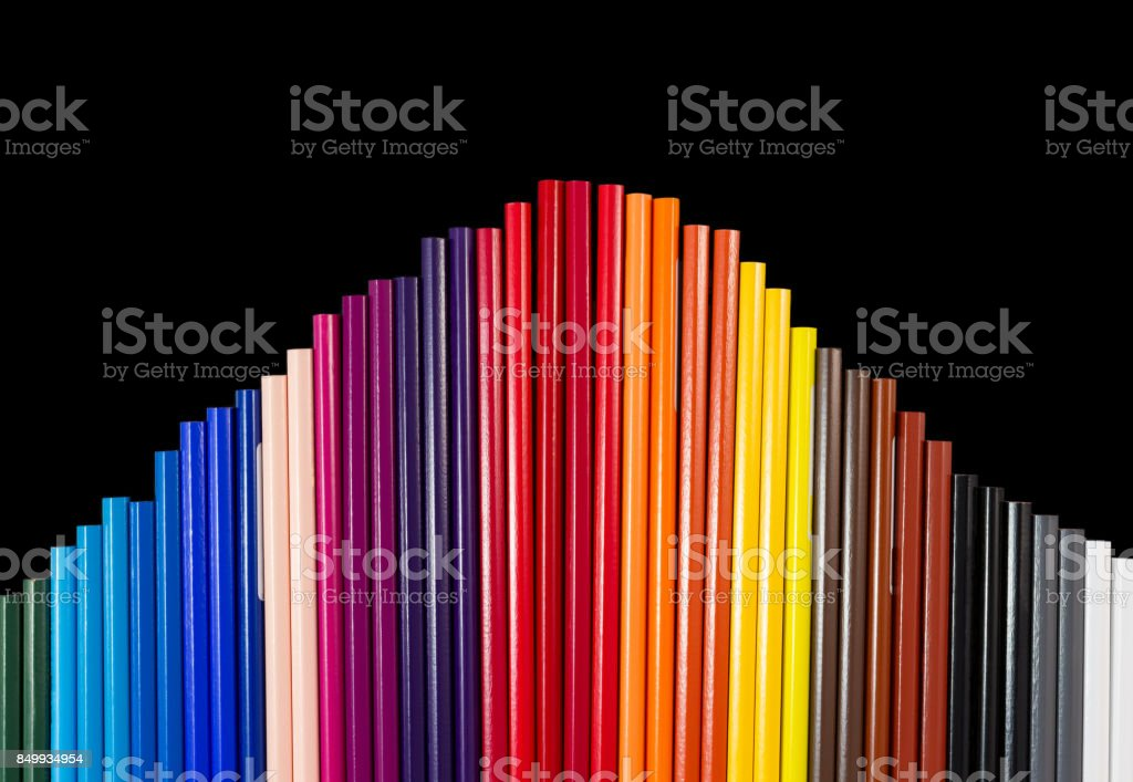 Color pencils in arc formation isolated on black background close-up stock photo