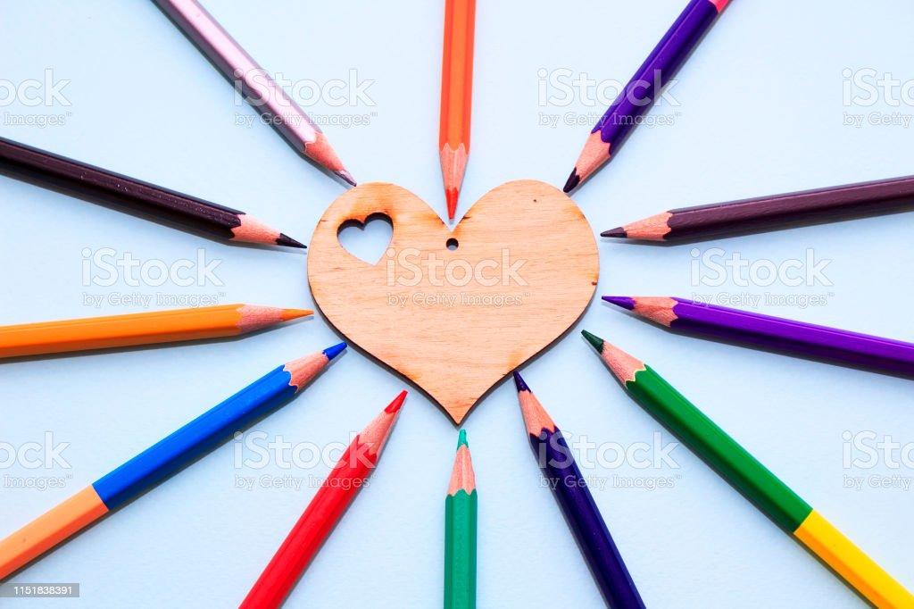 Color pencils in arrange in color wheel colors around wooden heart on...