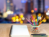 Color pencils in glass jar with notebook on wooden tabletop
